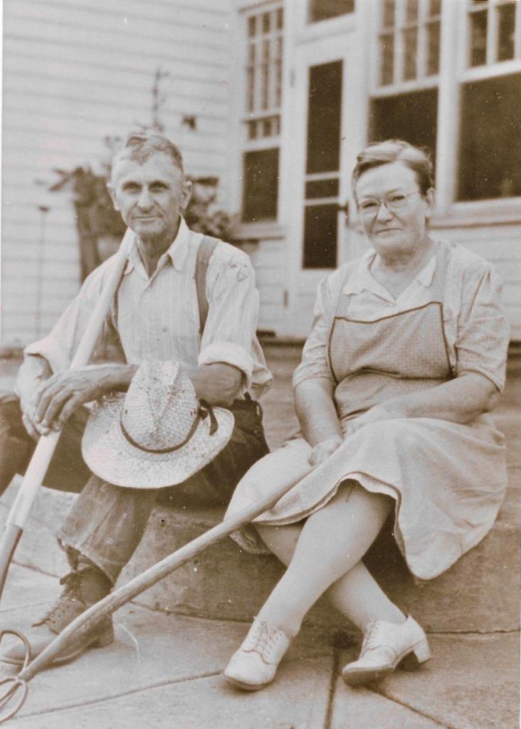 Grace and Carroll Raver, seated on a concrete step outside a house.  Carroll holds a shovel and a straw hat, Grace holds a rake.