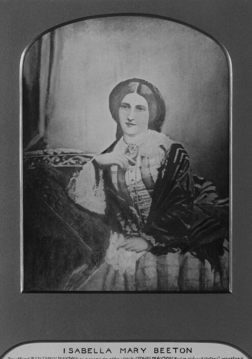 Photograph of Isabella Beeton, 1857.  Isabella wears a plaid dress and a dark shawl.  She is seated and rests her elbow on a cushion.