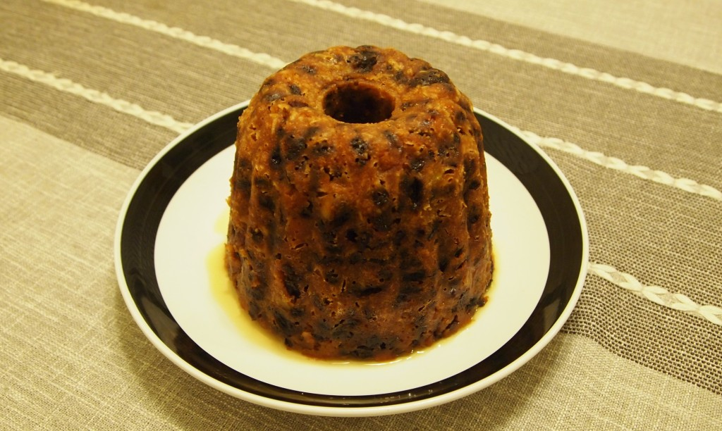 A Christmas pudding, turned out of a pudding mold and on to a plate
