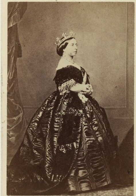 Photograph of Queen Victoria, 1861.  Queen Victoria stands facing right with her arms crossed in front of her.  She wears an elaborate dress and a crown.