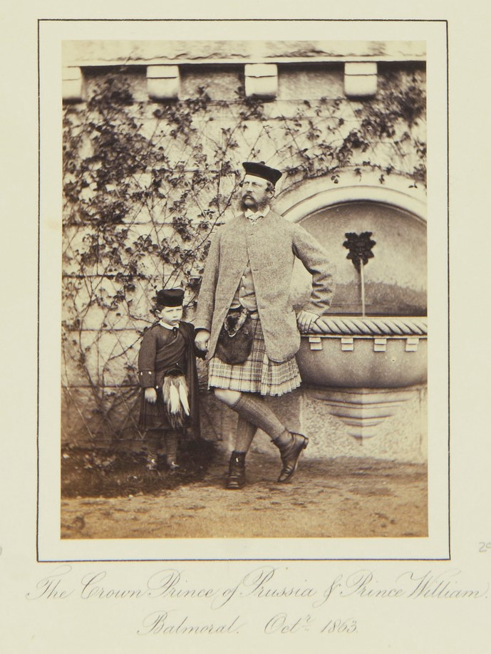 A little boy and a man, both wearing kilts, pose in front of an ivy-covered wall.