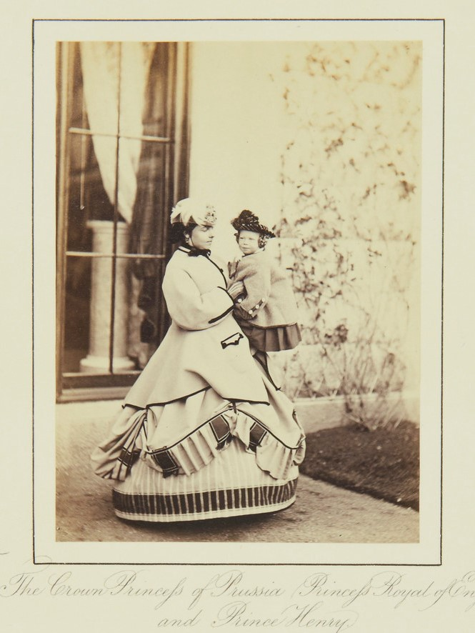 A woman wearing a dress with a hoop skirt holds a toddler and poses in front of a window.