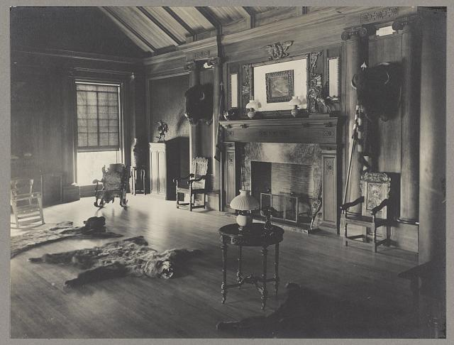 Image of a room with fireplace, several chairs, two stuffed bison heads, and two bearskin rugs.