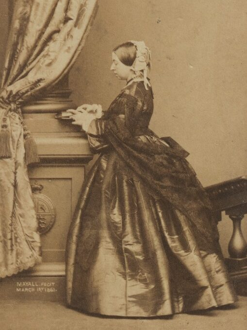 Photograph of Queen Victoria, 1861. Queen Victoria is wearing a dress and shawl, holding a book, and standing facing a column with her face in profile.